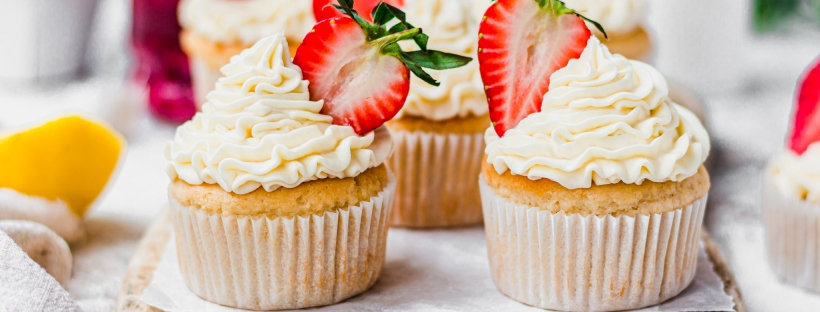 Two Vegan Lemon Strawberry Cupcakes on a wooden board